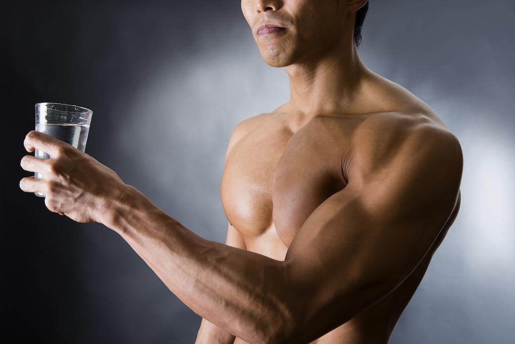水の入ったグラスを持つ筋肉質の男性